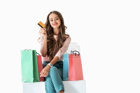 Photo for Smiling young woman holding golden credit card and sitting on white cube with shopping bags, isolated on white - Royalty Free Image