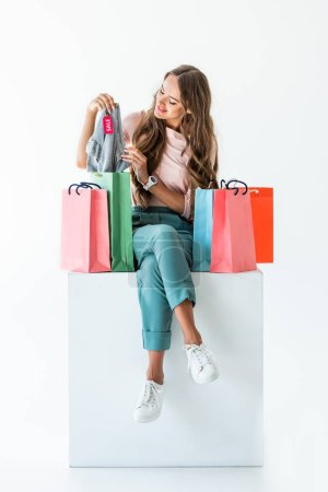 beautiful woman with shopping bags and clothes with sale tag, isolated on white