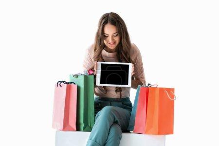 Photo pour Jeune fille souriante avec des sacs à provisions montrant la tablette avec un écran vide, isolé sur blanc - image libre de droit