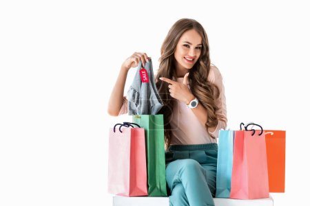 happy young woman with shopping bags pointing at clothes with sale tag, isolated on white
