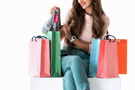 cropped view of woman with shopping bags showing clothes with sale tag, isolated on white