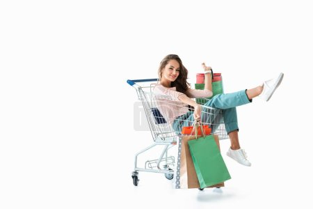 Photo for Happy beautiful girl sitting in shopping cart with bags, isolated on white - Royalty Free Image