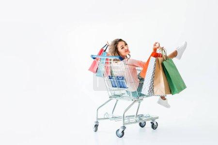 Photo pour Belle fille heureuse avec des sacs à provisions assis dans votre panier, isolé sur blanc - image libre de droit