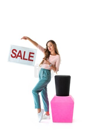 attractive young woman pointing at sale symbol near big nail polish, manicure concept, isolated on white
