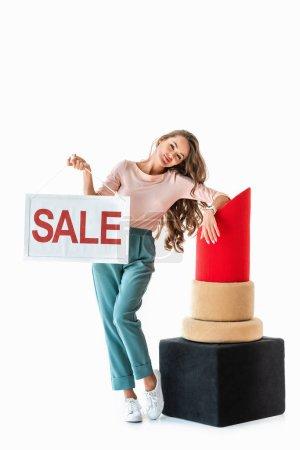 Photo pour Belle femme tenant symbole de vente près de gros rouge à lèvres rouge, concept de maquillage, isolé sur blanc - image libre de droit