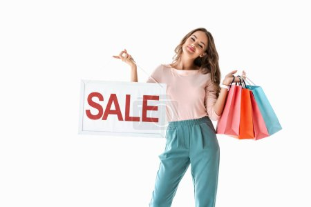 Photo for Beautiful smiling girl holding board with sale sign and shopping bags, isolated on white - Royalty Free Image