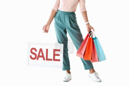 cropped view of beautiful girl holding board with sale sign and shopping bags, isolated on white
