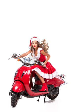 beautiful young woman in santa costume driving red scooter, isolated on white