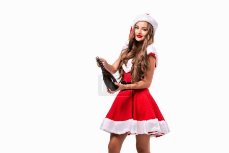 beautiful brunette girl in santa costume with champagne bottle, isolated on white