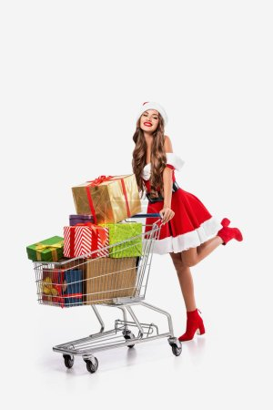 beautiful cheerful girl in santa costume with shopping cart full of gift boxes, isolated on white