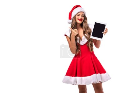 Photo for Happy girl in santa costume presenting tablet and showing thumb up, isolated on white - Royalty Free Image