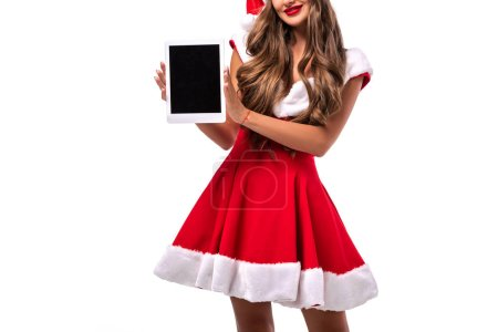Photo pour Vue recadrée de fille dedans santa costume affichage numérique appareil avec écran vide, isolé sur blanc - image libre de droit