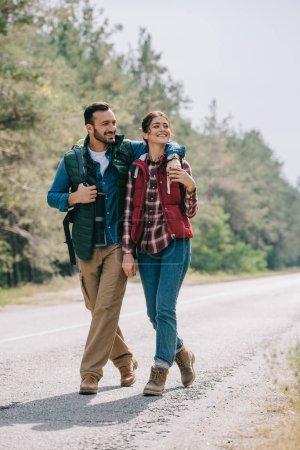 couple de voyageurs avec sacs à dos de marche sur route