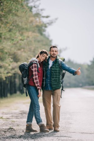 couple of travelers with backpacks hitchhiking on road