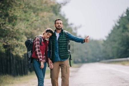 Photo for Couple of travelers with backpacks hitchhiking on road - Royalty Free Image