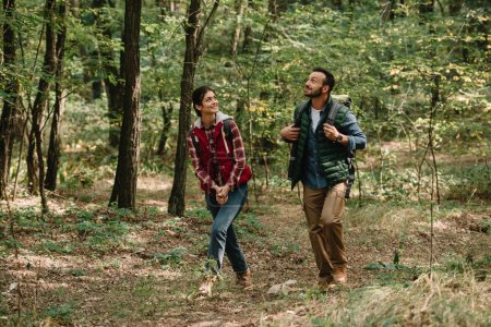 couple of smiling travelers with backpacks hiking in forest
