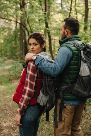 Photo for Man hugging woman while hiking in forest together - Royalty Free Image