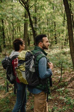 Photo pour Vue latérale de l'homme et la femme avec des sacs à dos de randonnée en bois ensemble - image libre de droit