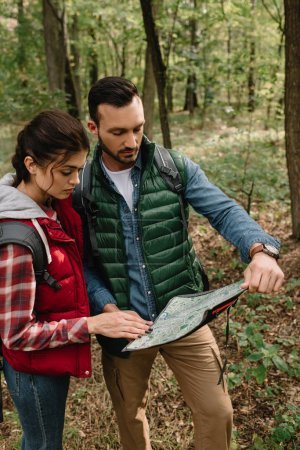 Photo for Man and woman looking for destination on map while hiking in forest together - Royalty Free Image