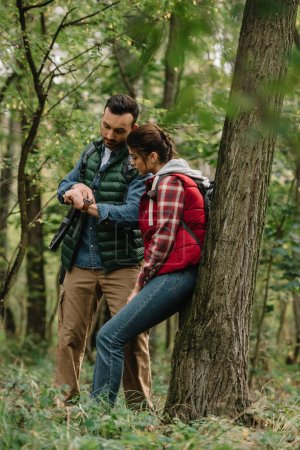 Photo pour Couple de voyageurs avec sacs à dos, vérifier de temps en forêt - image libre de droit