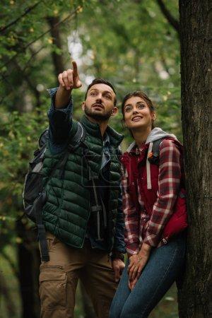 Porträt eines Mannes und einer Frau mit Rucksack, die beim Wandern im Wald wegschauen