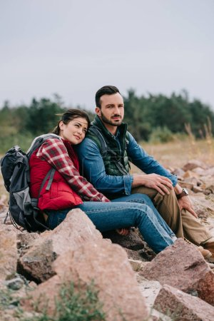 man and woman with backpacks resting on rocks on sandy beach