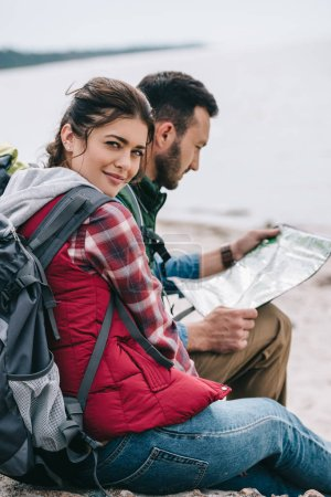 side view of hikers with map sitting on rocks on sandy beach