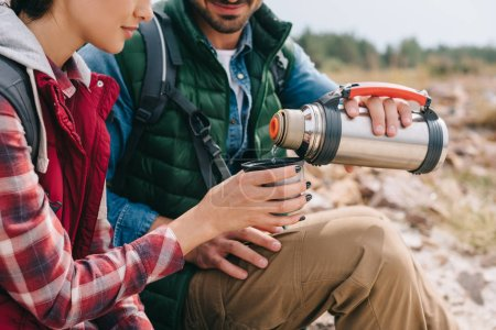 Photo for Partial view of couple of travelers with hot drink in thermos - Royalty Free Image