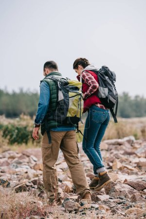 hikers with backpacks walking on stones