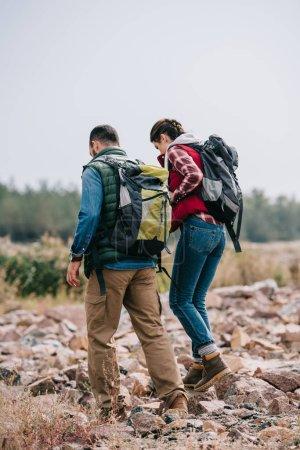 Photo pour Randonneurs avec sacs à dos, marche sur les pierres - image libre de droit
