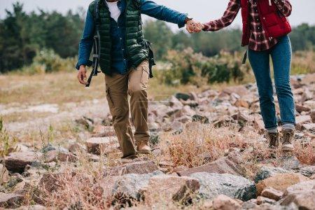 Photo pour Vue partielle des randonneurs avec des sacs à dos, main dans la main, marchant sur des pierres - image libre de droit