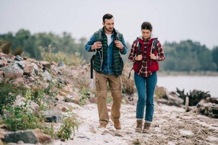 Photo pour Randonneurs avec sacs à dos, marcher ensemble sur la plage de sable fin - image libre de droit