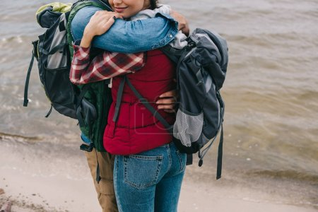 partial view of couple of hikers with backpacks hugging on sandy beach