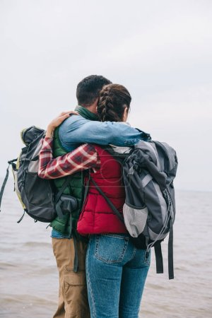 couple of hikers with backpacks hugging and looking at sea