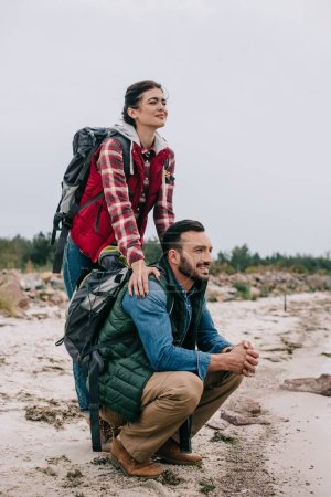 couple of hikers with backpacks on sandy beach