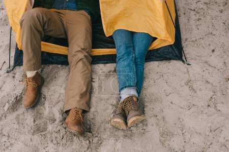 cropped shot of couple resting in camping tent on sandy beach