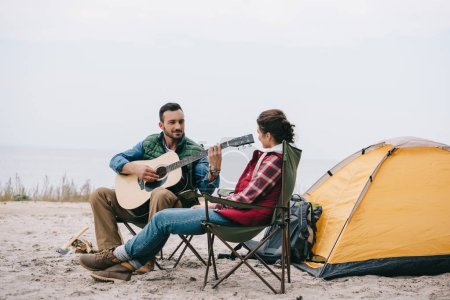 man playing acoustic guitar for wife on camping