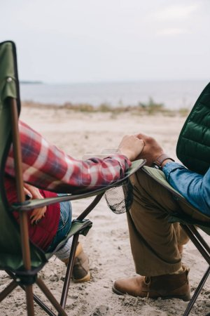 partial view of man and woman holding hands while enjoying camping together