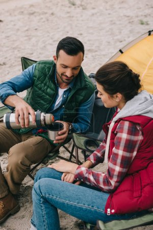 couple drinking hot tea during camping
