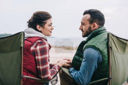 arrière de l'homme et la femme tenant par la main tout en appréciant le camping ensemble