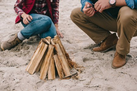 couple making campfire on sandy beach