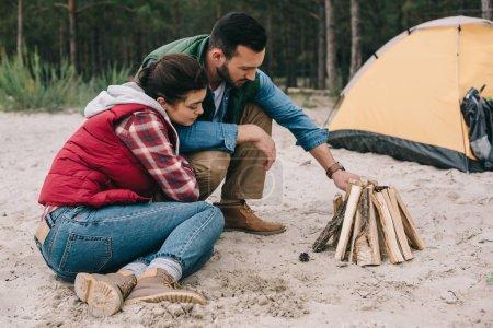 couple making campfire on sandy beach