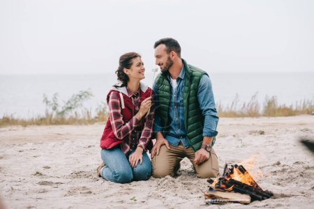 woman feeding husband with marshmallow at campfire on sandy beach