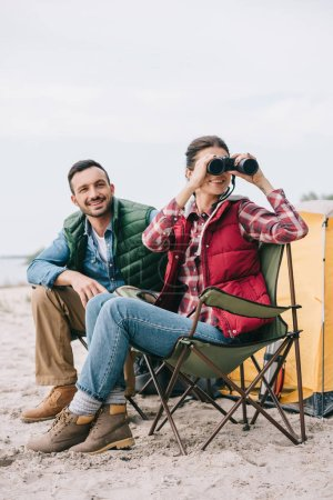 couple with binoculars resting on chairs on camping