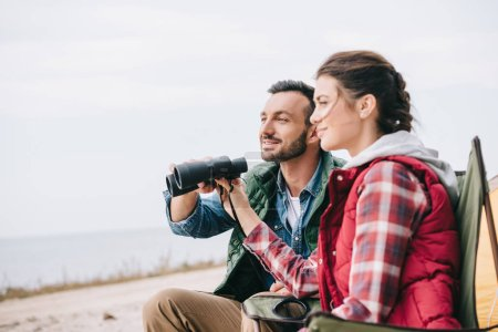 side view of couple with binoculars having camping