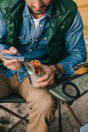 Photo for Cropped shot of traveler eating food from can during hiking - Royalty Free Image