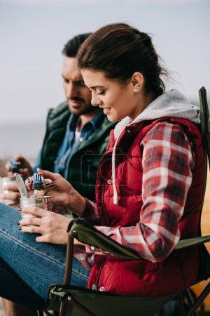 Photo pour Couple manger de la nourriture à partir de boîtes tout en ayant camping - image libre de droit