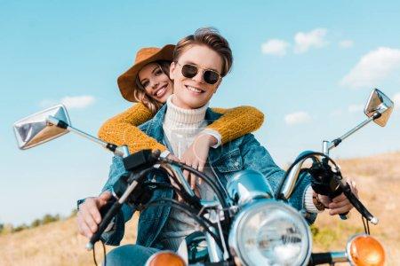 attractive girlfriend hugging boyfriend sitting on retro motorbike on meadow