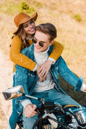 young girlfriend hugging boyfriend sitting on vintage motorbike on meadow