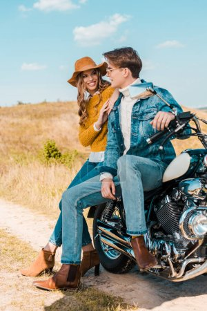 young couple looking at each other and sitting on retro motorbike